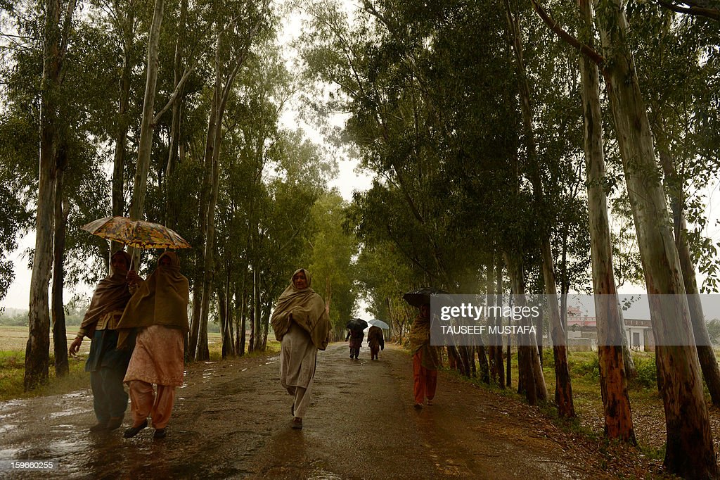 Indian villagers walk during a rain shower along the India-Pakistan border in Suchit-Garh, 36 kms southwest of Jammu on January 18, 2013. On both sides of the de facto border in Kashmir, villagers living on one of the world's most dangerous flashpoints have special reason to fear the return of tension between India and Pakistan. AFP PHOTO/Tauseef MUSTAFA
