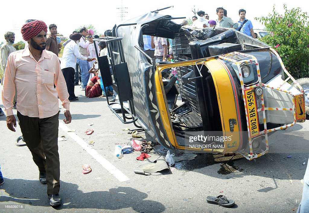 Indian villagers walk past an overturned auto rickshaw near Khasa Village about 20 Km from Amritsar on April 3, 2013. Six people were injured, when an auto rickshaw collided with another rickshaw on the way to India-Pakistan Wagah border.