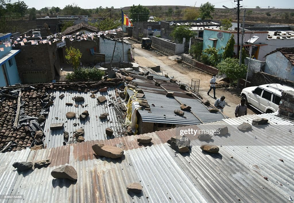 Indian villagers walk past houses struck by debris following a fire at an ammunition depot in Pulgaon some 100kms from Nagpur on May 31, 2016. A massive fire that erupted at one of India's largest military ammunition depots May 31 killed at least 16 soldiers and firefighters, reigniting safety concerns about military equipment and installations. The blaze broke out in the early hours at the high-security facility which stores bombs, grenades and other ordnance outside the central city of Pulgaon. Flames lit up the night sky. / AFP / STR