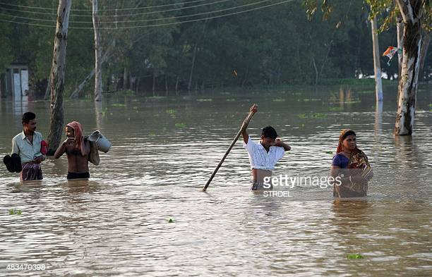 Indian villagers walk through floodwaters in Hooghly District some 90kms from Kolkata on August 9 as heavy monsoon rainfall continues across the...