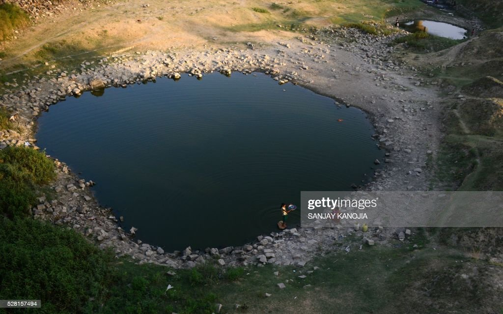 Indian villagers wash clothes in a pool in the shrunken Mansaita River near Allahabad on May 4, 2016. Some 330 million people are suffering from drought in India, the government has said, as the country reels from severe water shortages and desperately poor farmers suffer crop losses. / AFP / SANJAY