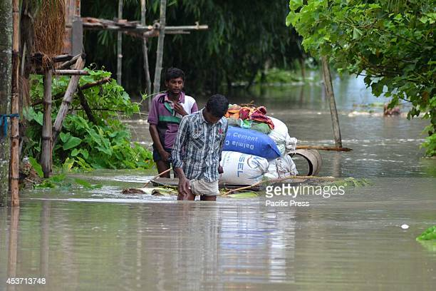 Indian Villagers with their belongings going to a higher place after waters of the River Barhmaputra entered their houses at Bhurbandha in Nagaon...