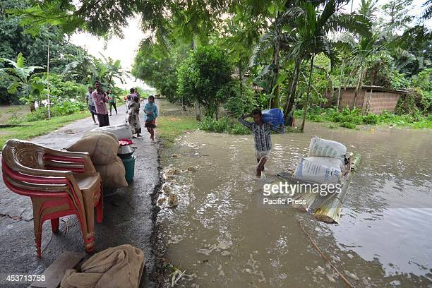 Indian Villagers with their belongings going to higher places after waters of River Barhmaputra entered their houses at Bhurbandha in Nagaon district...