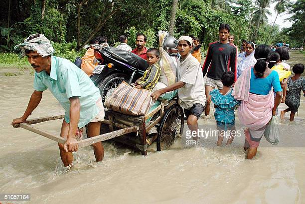 Indian villagers with their household goods walk through floodwaters in the village of BoromaNalbari District some 70km west of Guwahati 14 July 2004...