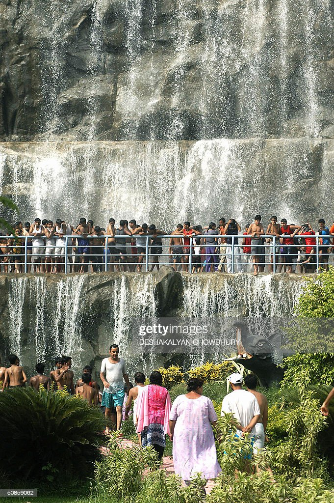 Indian visitors enjoy the cooling effect of water from a 25 metre (75 feet) high waterfall at 'Aquatica' a water amusement park at Hathgachia, near Calcutta, 20 May 2004. A heatwave which is sweeping across northern India with temperatures being recored in excess of 45 degrees Celcius (118 Degrees Fahrenheit) has resulted in an increase of visitors to establishments such as 'Aquatica'. AFP PHOTO/Deshakalyan CHOWDHURY