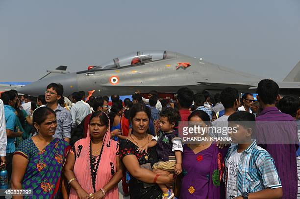 Indian visitors have their photograph taken in front of an Indian Air Force aircraft during the Air Force Day parade at the Hindon Air Force Station...