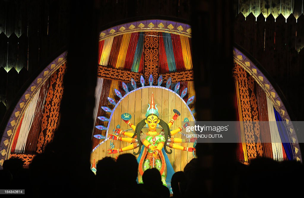 Indian visitors look at an idol of Hindu goddess Durga in preparation for the upcoming Hindu festival Durga Puja in Siliguri on October 18, 2012. The five-day period of worship of Durga, who is attributed as the destroyer of evil, commences on October 20. AFP PHOTO/ Diptendu DUTTA