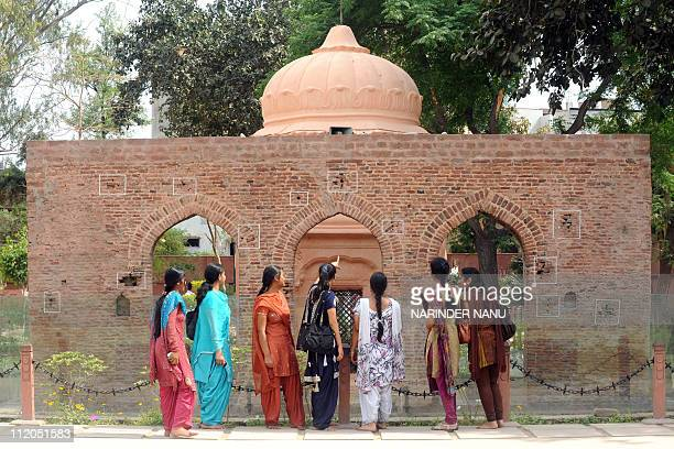 Indian visitors look at the bullet ridden wall at the historical site of the Jallianwala Bagh massacre in Amritsar on April 12 2011 The Amritsar...
