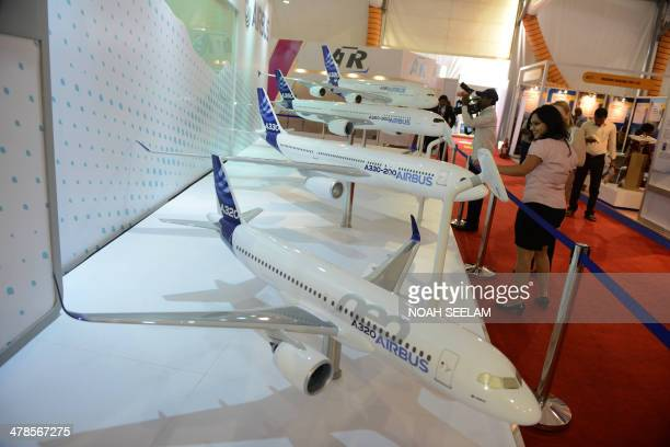 Indian visitors looks at models of Airbus series aircraft on display in an exhibitors venue at the India Aviation 2014 airshow at Begumpet Airport in...