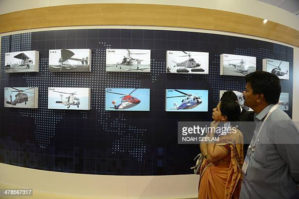 Indian visitors looks at the photos of the history of helicopters displayed in an exhibitors venue at the India Aviation 2014 airshow at Begumpet...