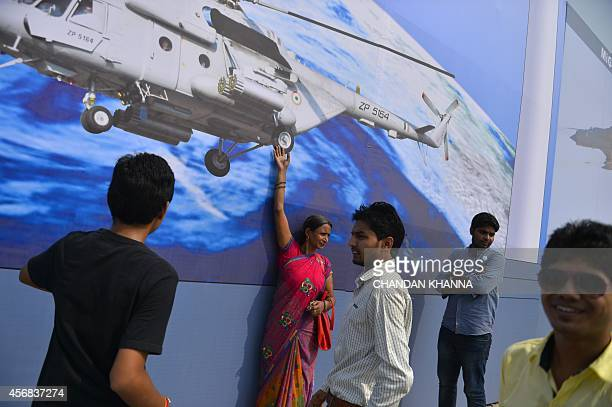 Indian visitors take photographs in front of an Indian Air Force billboard during the Air Force Day parade at the Hindon Air Force Station in...