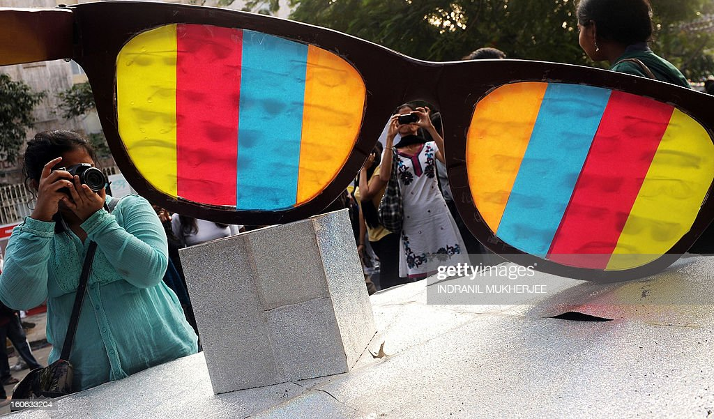 Indian visitors take photographs of an art installation made from over sized spectacles at the annual Kala Ghoda Arts Festival in Mumbai on February 4, 2013. The nine-day art festival held every year since 1999 featuring a variety of arts, cultures and culinary delights, has grown in stature and popularity, attracting visitors and participants from India and the world. AFP PHOTO/ Indranil MUKHERJEE