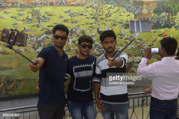 Indian visitors takes selfie photographs in front of a painting depicting the Jallianwala Bagh massacre on its 98th anniversary at Jallianwala Bagh...