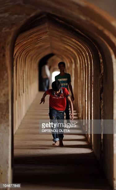 Indian visitors walk around the Bara Imambara mosque as a calm transcends over the area in Lucknow on October 3 2010 Schools shops and businesses...