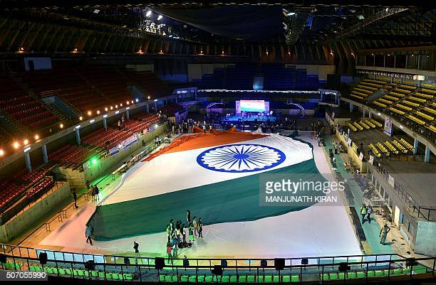 Indian visitors walk past a worldrecord attempt to stich an Indian flag in Bangalore on January 27 2016 The flag measured over 30000 square feet and...