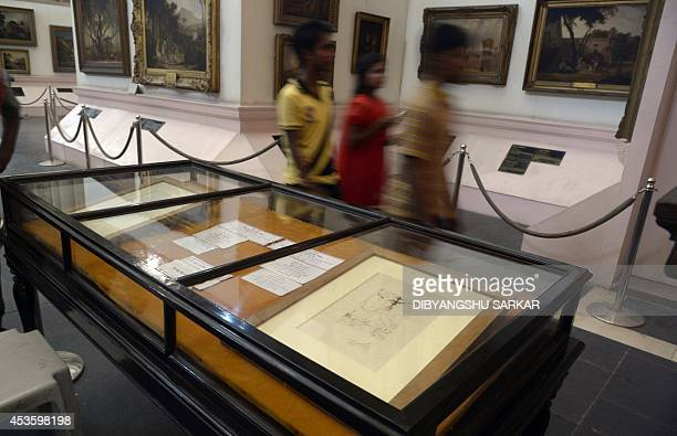 Indian visitors walk past displays of two artworks by Salvador Dali in Durbar Hall of The Victoria Memorial in Kolkata on August 14 2014 The two...