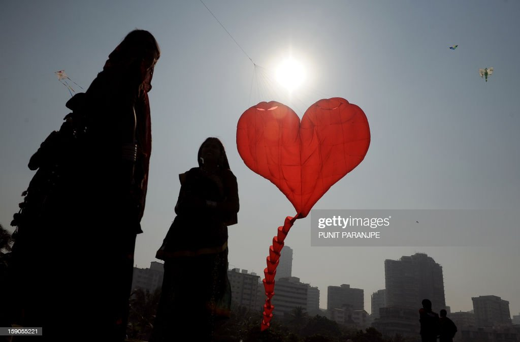 Indian visitors watch a heart shaped kite fly during the International Kite festival on the lawns of Priyadarshani park in Mumbai on January 7, 2013. Kite enthusiasts from different countries are participating in the day-long festival.