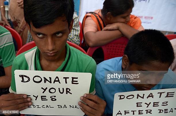 Indian visually challenged youth hold posters during a campaign to create awareness about eye donation in Kolkata on August 27 2014 According to a...