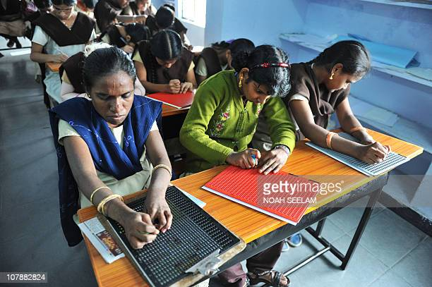 Indian visually impaired students M Adi Lakshmi N Neeraja and K Swaroopa write during an economy class using the Braille system at Sai Junior College...