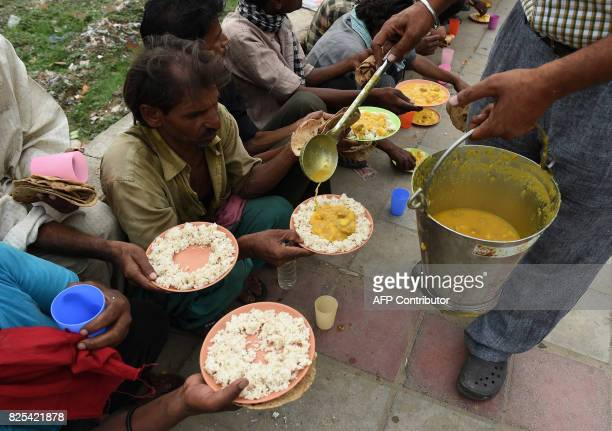 Indian volunteer from the Veerji Da Dera Sikh community Kamaljeet Singh distributes free food to homeless people in New Delhi on August 2 2017 Delhi...