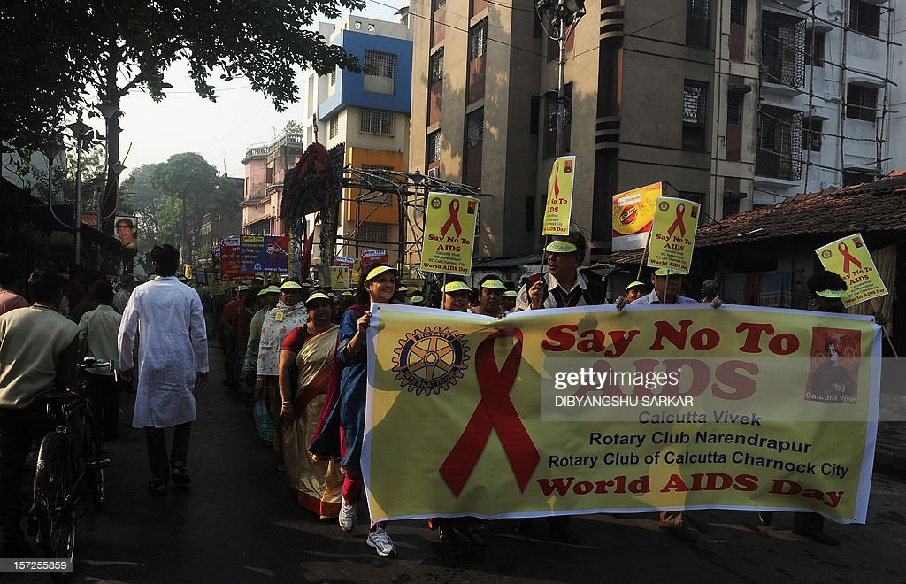 Indian volunteers and members of a social organisation holds placards with HIV/AIDS awareness messages during a rally to celebrate World AIDS Day in Kolkata on December 1, 2012. The UNAIDS agency says some 2.5 million Indians are living with HIV, many of them ostracised by their communities. AFP PHOTO/Dibyangshu SARKAR