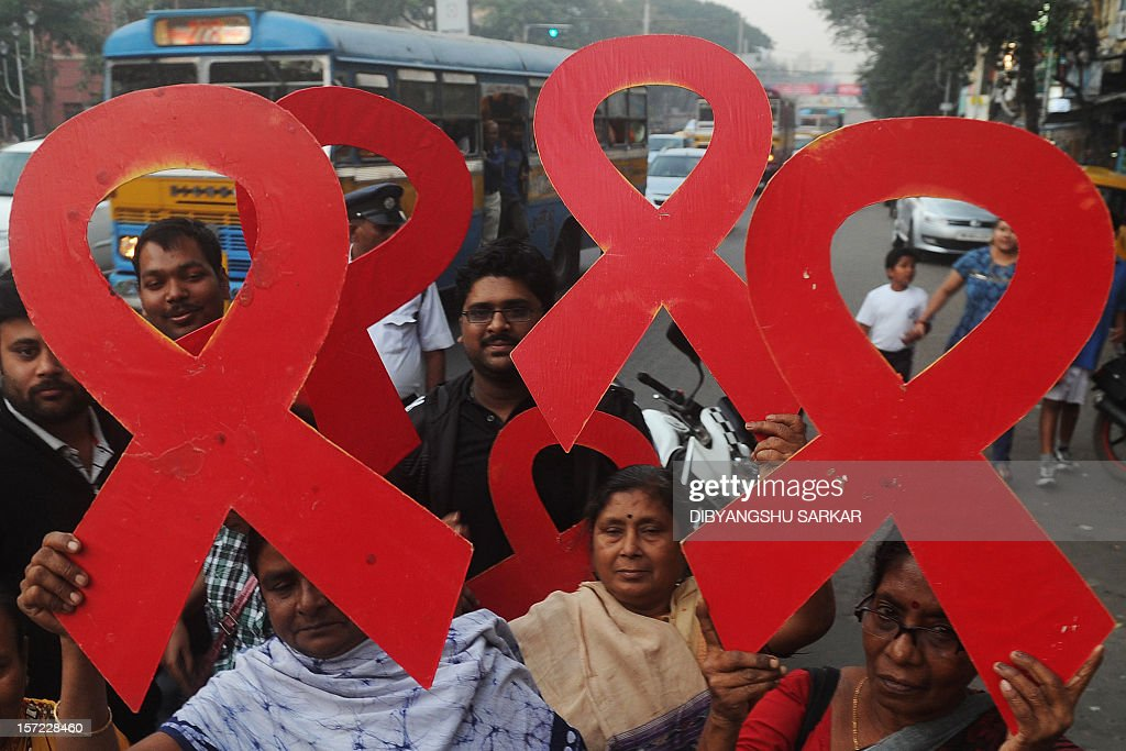 Indian volunteers and the members of a social organisation holds ribbon shaped placards for an HIV/AIDS awareness messages during rally in Kolkata on November 30, 2012, on the eve of World AIDS Day. The UNAIDS agency says some 2.5 million Indians are living with HIV, many of them ostracised by their communities. AFP PHOTO/Dibyangshu SARKAR / AFP / DIBYANGSHU SARKAR