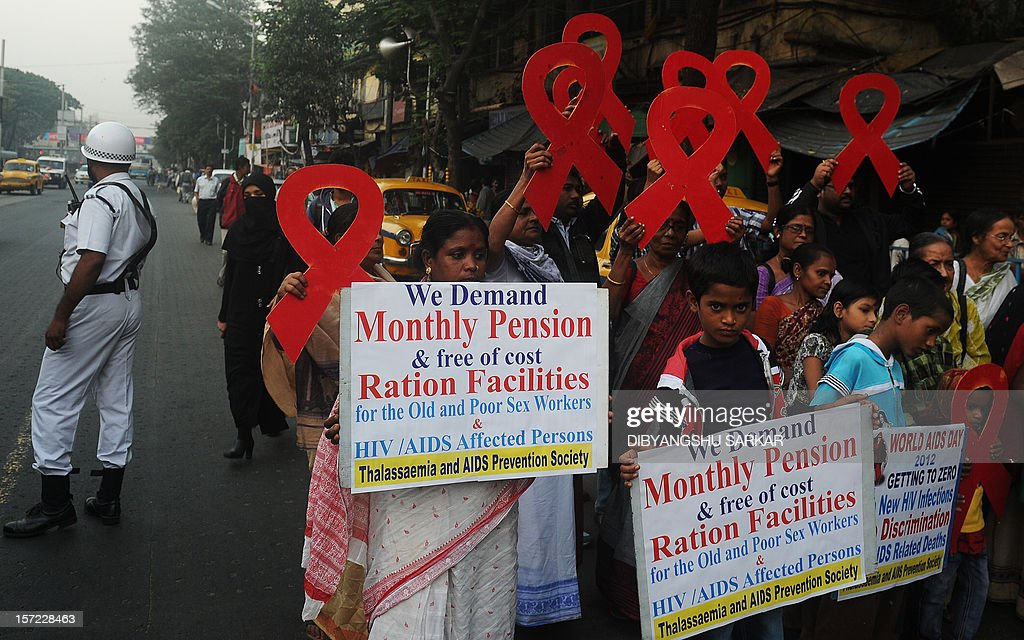 Indian volunteers and the members of a social organisation holds ribbon shaped placards for an HIV/AIDS awareness messages during rally in Kolkata on November 30, 2012, on the eve of World AIDS Day. The UNAIDS agency says some 2.5 million Indians are living with HIV, many of them ostracised by their communities. AFP PHOTO/Dibyangshu SARKAR
