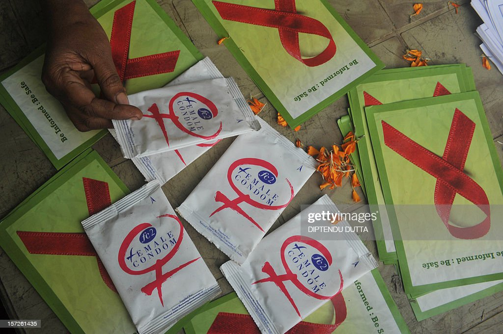 Indian volunteers and the members of the West Bengal Voluntary Health Association (WBVHA) distribute condoms on World Aids day in Siliguri on December 1,2012. The UNAIDS agency says some 2.5 million Indians are living with HIV, many of them ostracised by their communities. AFP PHOTO/ Diptendu DUTTA