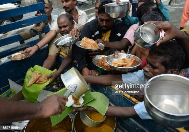 Indian volunteers distribute food to residents in a flooded area after heavy monsoon rains in Chennai on November 3 2017 The arrival of the northeast...