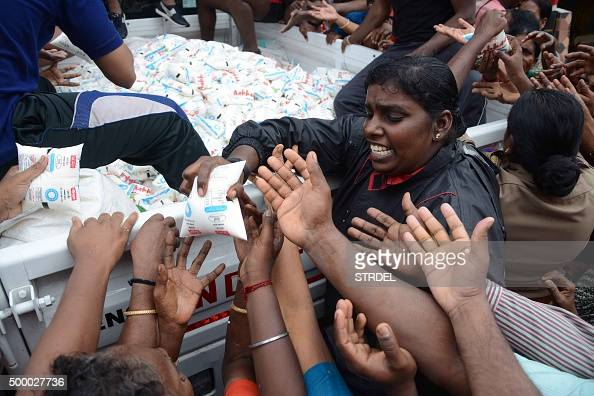 Indian volunteers distribute packets of milk from the back of a vehicle to flood affected residents in Chennai on December 5 2015 Thousands of...