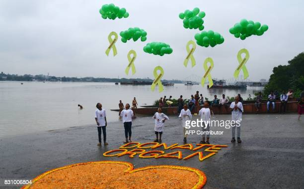 Indian volunteers release balloons next to a floral decoration on the bank of the river Ganges to promote awareness about organ donation in Kolkata...