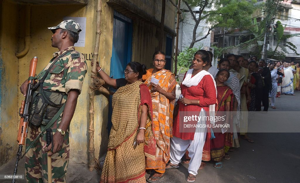 Indian voters are supervised by a paramilitary soldier as they wait to cast their ballots in state assembly elections at a polling station at a polling station in Kolkata on April 30, 2016. State assembly elections in West Bengal are taking place from April 4 to May 5. / AFP / Dibyangshu SARKAR