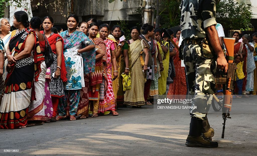 Indian voters are watched by a paramilitary soldier as they wait to cast their ballots in state assembly elections at a polling station at a polling station in Kolkata on April 30, 2016. State assembly elections in West Bengal are taking place from April 4 to May 5. / AFP / Dibyangshu SARKAR