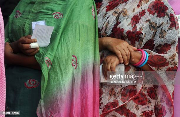 Indian voters hold their identity cards as they queue at a voting centre in the final stage of state assembly elections in the Bihar village of...