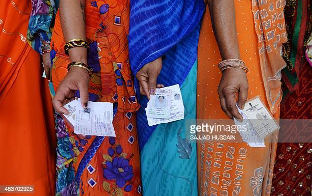 Indian voters pose with their voting slips as they stand in a line to cast their vote outside a polling station at Dabua village on the outskirts of...