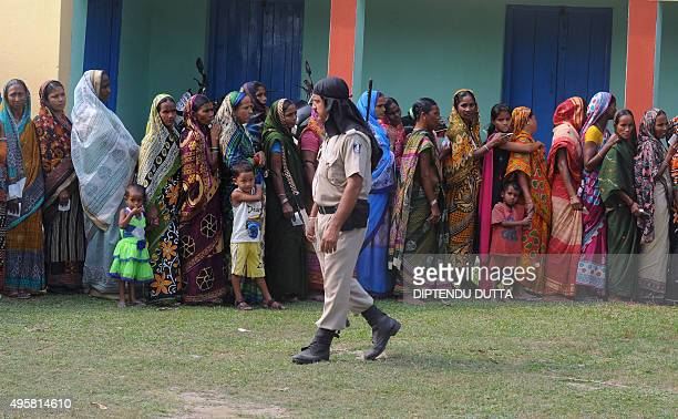 Indian voters queue to cast their ballots at a voting centre in the final stage of state assembly elections in the Bihar village of Galgalia in...