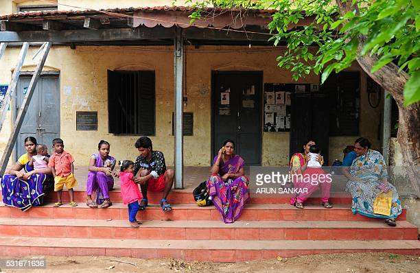 Indian voters sit with children as they wait to cast their ballots at a polling station in Chennai on May 16 during voting in state assembly...
