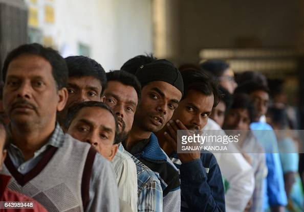 Indian voters wait in a queue for their turn to vote at a polling station in the Naini area on the outskirts of Allahabad during the fourth phase of...