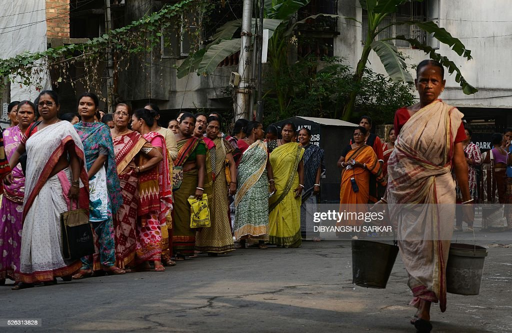 Indian voters wait to cast their ballots in state assembly elections at a polling station at a polling station in Kolkata on April 30, 2016. State assembly elections in West Bengal are taking place from April 4 to May 5. / AFP / Dibyangshu SARKAR