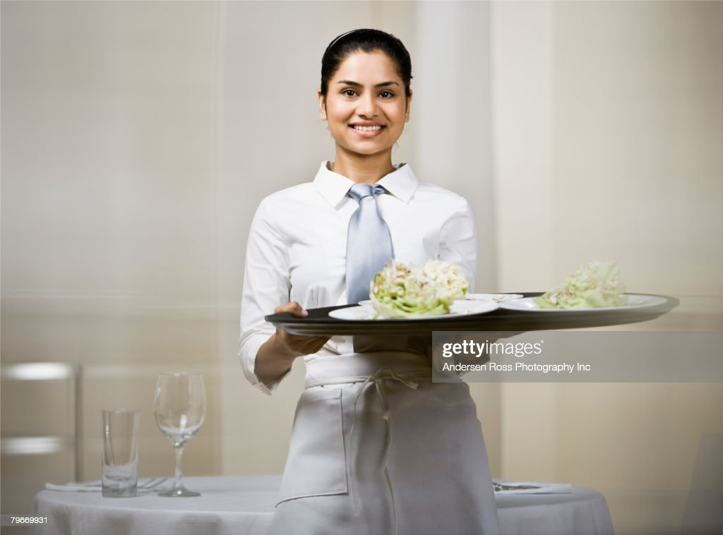 Indian waitress carrying tray of food : Stock Photo