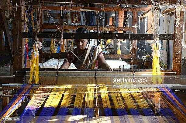Indian weaver Andra Jyothi weaves a silk saree on a handloom in a workshop at Bhoodan Pochampally in Nalgonda District some 55kms from Hyderabad on...