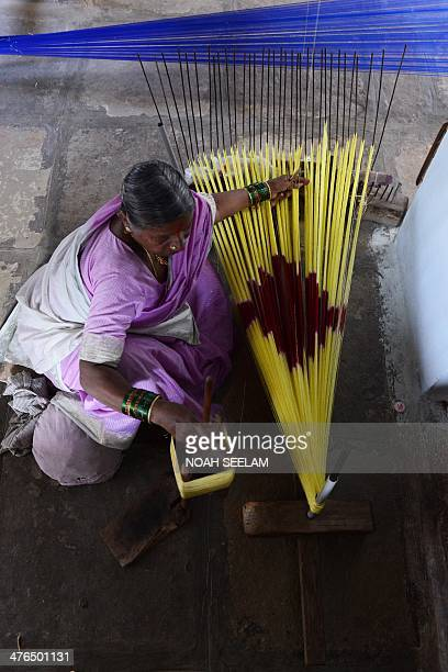 Indian weaver Joggu Saroja prepares silk coloured threads prior to weaving a saree on a handloom in a workshop at Bhoodan Pochampally in Nalgonda...