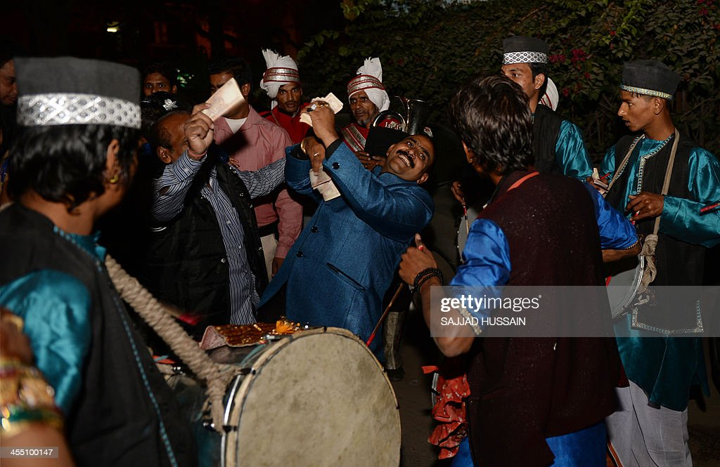 Indian wedding guests and relatives of the groom dance during a marriage ceremony on the sequential date of 11/12/13 in New Delhi on December 11, 2103. 11/12/13 is the last sequential date this century.