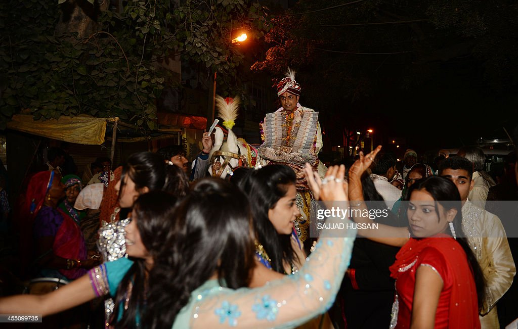 Indian wedding guests dance during a marriage ceremony as the groom rides a processional horse on the sequential date of 11/12/13 in New Delhi on December 11, 2103. 11/12/13 is the last sequential date this century.