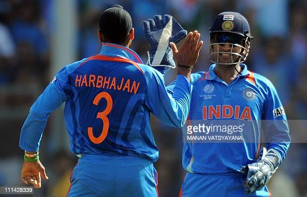 Indian wicketkeeper and captain Mahendra Singh Dhoni celebrates with Indian offspinner Harbhajan Singh the dismissal of Sri Lankan batsman...