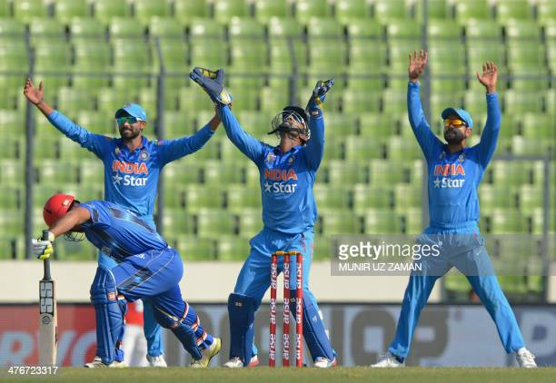 Indian wicketkeeper Dinesh Karthik captain Virat Kohli and Ravindra Jadeja unsuccessfully appeal for the dismissal of Afghan batsman Samiullah...