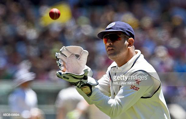 Indian wicketkeeper Mahendra Singh Dhoni catches the ball from the outfield during the second day of the third cricket Test match against Australia...