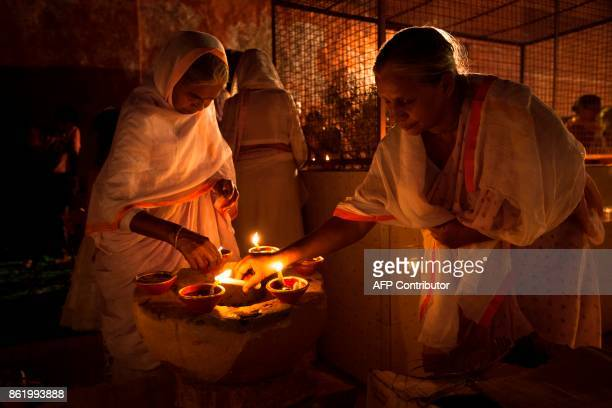 Indian widows light earthen lamps or 'diyas' during Diwali celebrations at Gopinath temple in Vrindavan on October 16 2017 Diwali the Festival of...