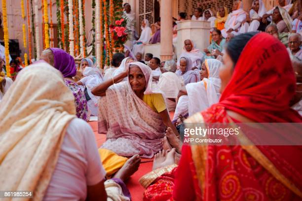 Indian widows wait before the start of the remarriage of Vinita Devi a former widow at Gopinath temple in the Vrindavan on October 16 2017 India has...