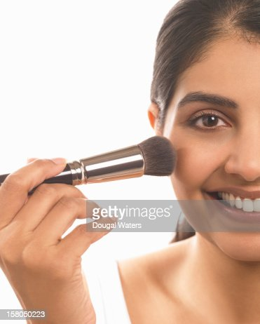 Indian woman applying make up to face. : Stock Photo